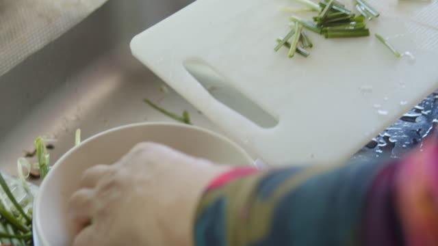 slicing scallion in the kitchen - scallion stock videos & royalty-free footage