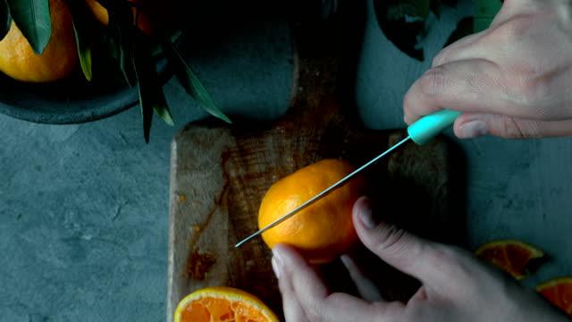 stockvideo's en b-roll-footage met mandarijn/sinaasappel vrucht snijden - snijplank