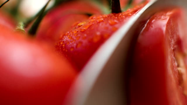 stockvideo's en b-roll-footage met slicing tomato macro shot - rijp voedselbereiding