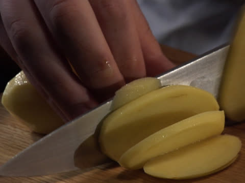 slicing two peeled potatoes - unknown gender stock videos & royalty-free footage