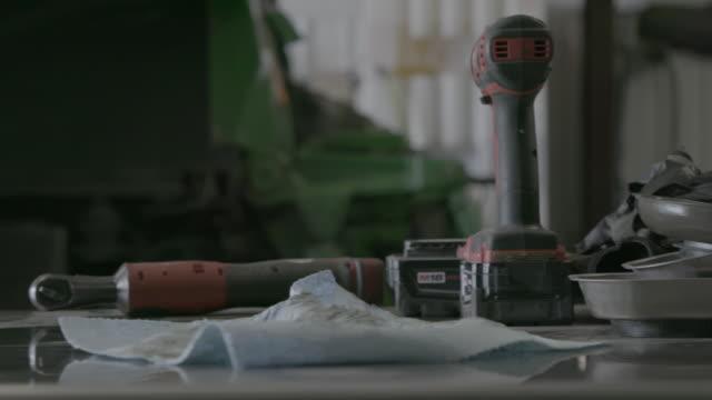 slide across tools on work bench - attrezzi da lavoro video stock e b–roll