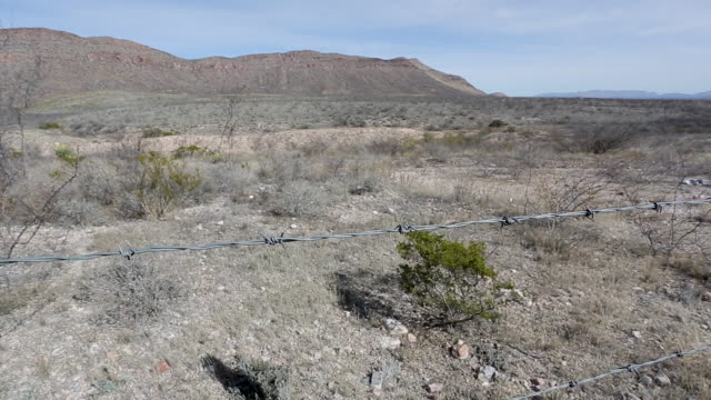 slide along barbed wire fence in the desert, medium close - southwest usa video stock e b–roll