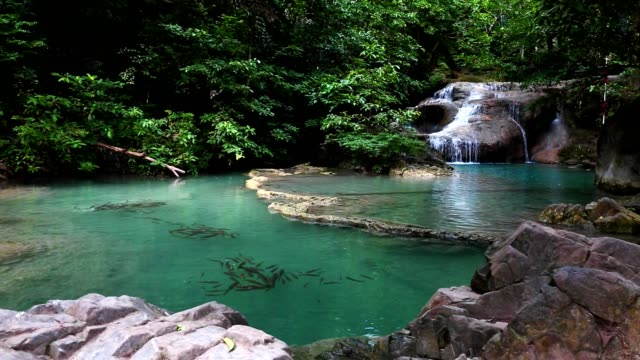 Slide dolly waterfall in jungle with beautiful emerald green water.