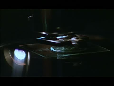 various cu ecu slide moving around on lit stage of atomic force microscope. - vetreria da laboratorio video stock e b–roll