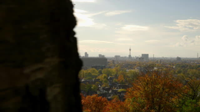 slide revealing duesseldorf city panorama behind autumn forest