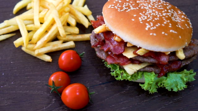 slide shot of bacon burger and cherry tomatoes. - tipo di panino video stock e b–roll