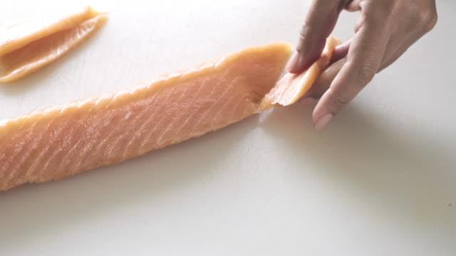 サケを小さくスライスする女性のスライダーショット。 - 切る点の映像素材/bロール