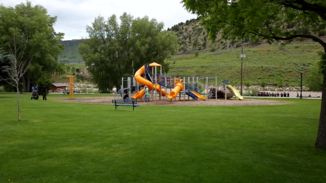 slider wide shot of park and playground - playground stock videos & royalty-free footage