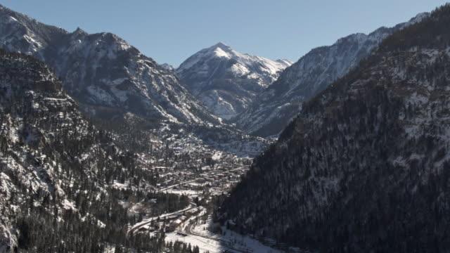 青空の下でコロラド州ユーレイの上の木の雪に覆われた森林とサンファン山脈 (ロッキー山脈) の雪のかぶった頂上の空中ドローン ショットをスライド - ユアレイ市点の映像素材/bロール