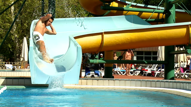 hd slow motion: sliding down winding waterslide - water slide stock videos & royalty-free footage
