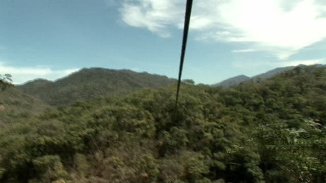 pov, sliding down zipline over green hills, mexico - ロープスライダー点の映像素材/bロール