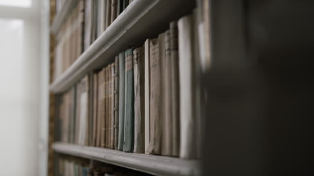 sliding shot of a bookshelf in a library - bookshelf stock videos & royalty-free footage