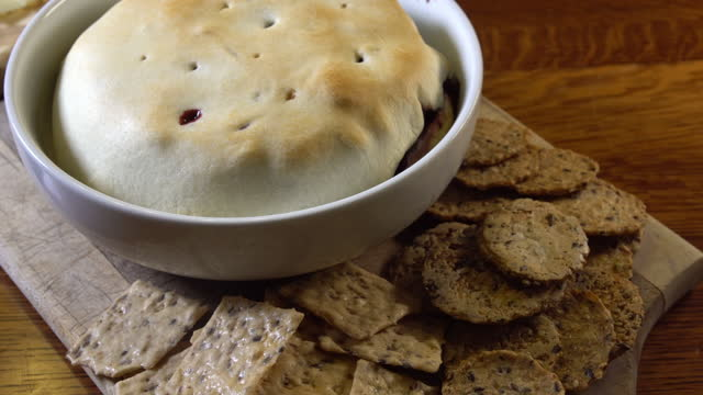 焼きたてのブリーチーズディップのクラッカー入りスライディングショット - ブリーチーズ点の映像素材/bロール