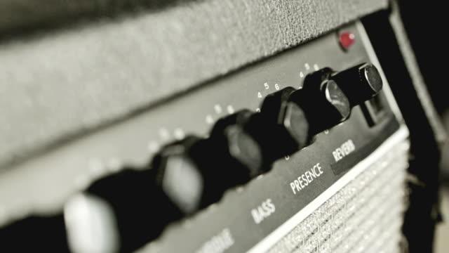 rutschen auf der verstärker knobs und steckdosen - moderne rockmusik stock-videos und b-roll-filmmaterial