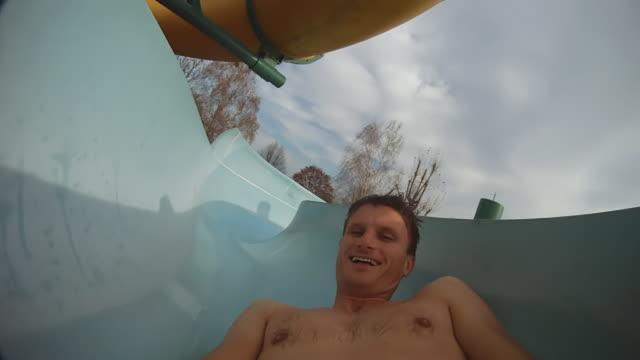 vídeos de stock, filmes e b-roll de hd: de trás para frente, em correr com tobogã aquático sinuoso - tobogã d'água