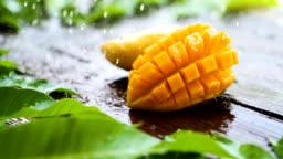 Sliece fresh yellow mango tropical fruit with rain drop on wooden table