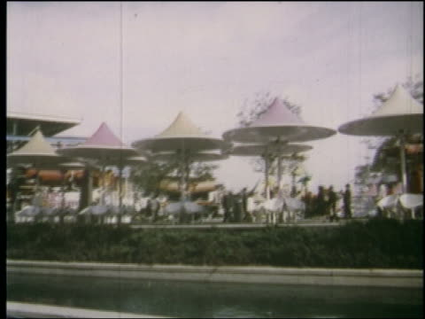 1964 slight side point of view chairs with colored umbrellas above at ny world's fair - medium group of objects stock videos & royalty-free footage