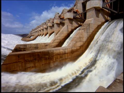 Slight PAN of water flowing thru dam / Itaipu, Parana, Brazil