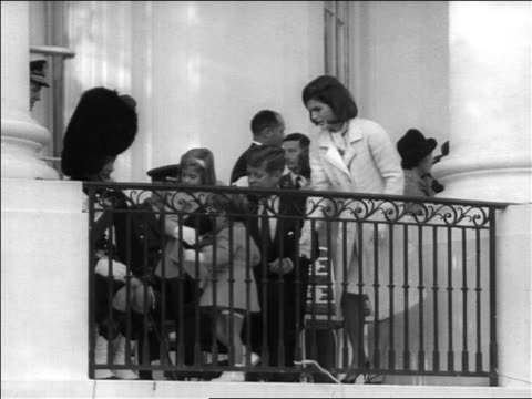 slight zoom out john + jacqueline kennedy with children sitting on balcony / newsreel - jackie kennedy stock videos & royalty-free footage