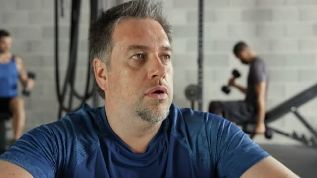 slightly overweight man catching his breath after an extensive exercise in the gym - 40 44 anni video stock e b–roll