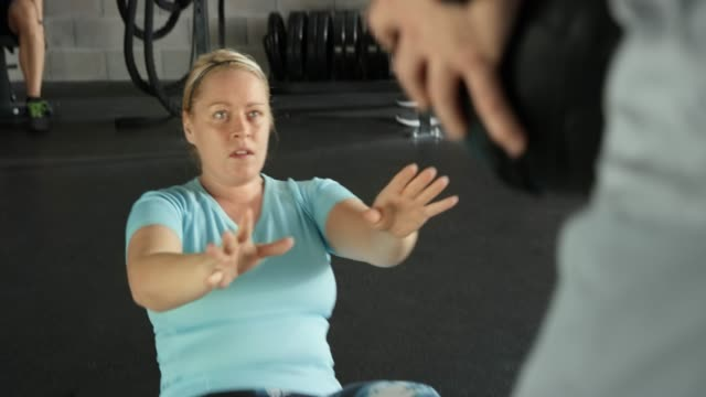 slightly overweight woman doing exercises with a medicine ball with her trainer in the gym - overweight active stock videos & royalty-free footage