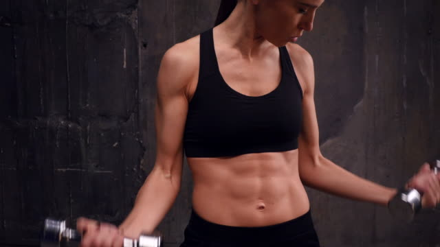 Slim athletic female with dumbbells performing pump up exercise for biceps