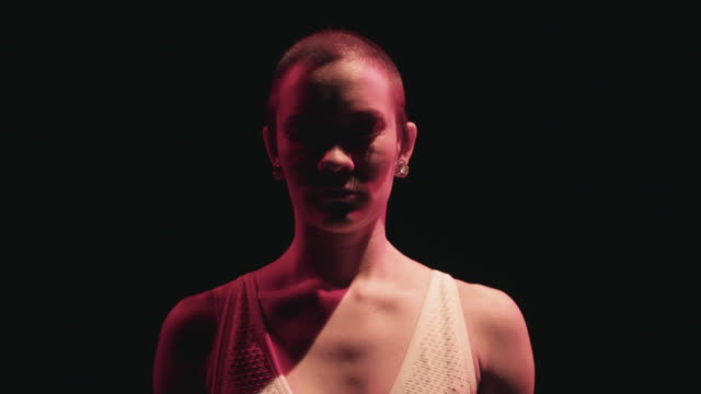 a slim bald female circus performer performs her routine in a dark studio space - sensuality stock videos & royalty-free footage