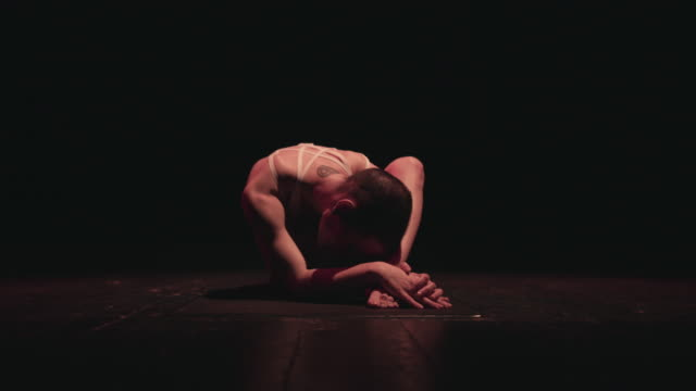 a slim bald female circus performer performs her routine in a dark studio space - the human body stock videos & royalty-free footage