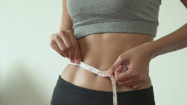 slim woman measuring her thin waist - abdominal muscle stock videos & royalty-free footage