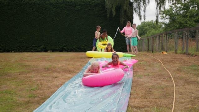 slip ' n ' slide mit freunden - wasserrutsche stock-videos und b-roll-filmmaterial