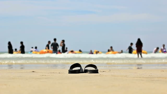 ms slipper shoes behind people enjoying holiday on daecheon beach / boryeong, chungcheongnam-do, south korea - stare in piedi video stock e b–roll