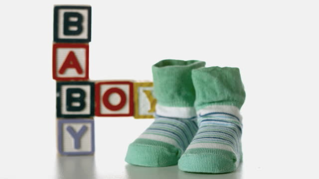 slippers falling besides baby blocks on white background - capital letter stock videos & royalty-free footage