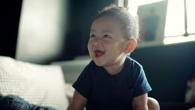 Slo mo : A baby boy (6-11 months) laughing and having fun on a bed inside a home. Thailand.