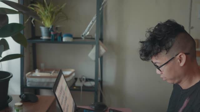 slo mo:ベッドルームでラップトップを使用して自宅から働くアジアのインディーズの男。 - 30代点の映像素材/bロール
