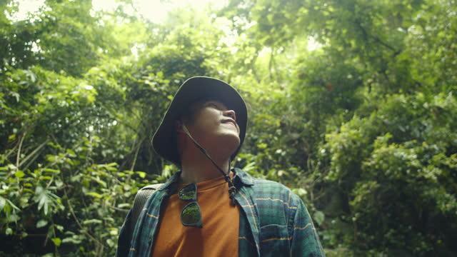 vidéos et rushes de slo mo : homme de touriste asiatique regardant vers le haut la nature dans la forêt. - thaïlande