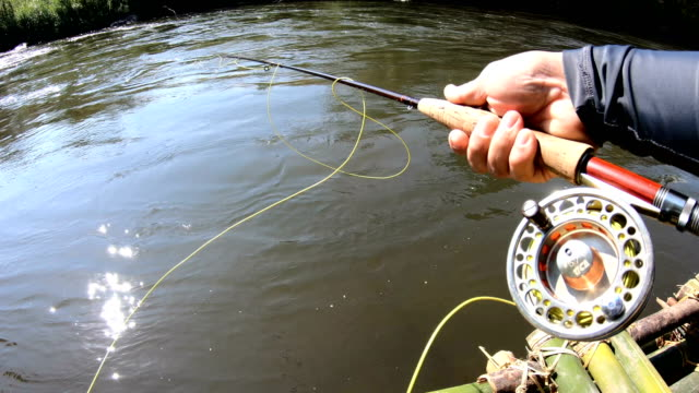 slo mo fly fishing on bamboo raft. - fishing rod stock videos & royalty-free footage