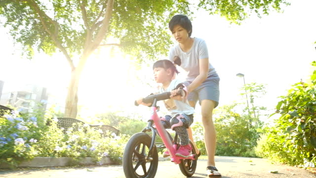 Slo Mo Girls riding a bicycle with her mother