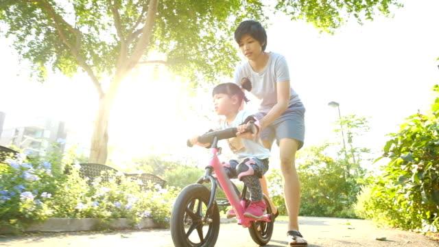 Slo Mo Girls conduisant un vélo avec sa mère