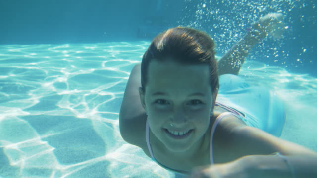 slo mo happy girl swimming underwater in a swimming pool - underwater camera stock videos & royalty-free footage