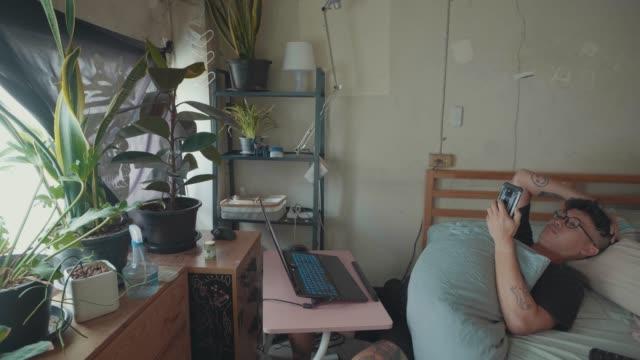 slo mo: ベッドに座ってラップトップを使用して自宅から働く怠惰なアジア人の男。 - 30代点の映像素材/bロール