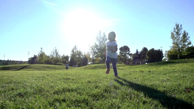 vídeos de stock e filmes b-roll de slo mo little girl running in the park - parque infantil