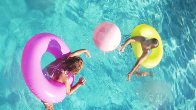 slo mo sisters playing together in a swimming pool - swimming pool stock videos & royalty-free footage