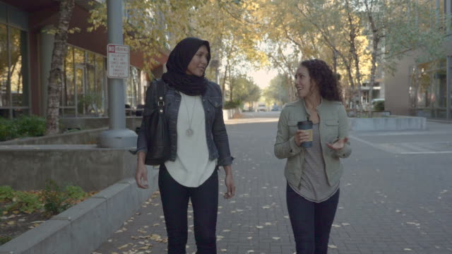 slo mo: two women of middle eastern decent out for a walk in an urban area - hijab stock videos and b-roll footage
