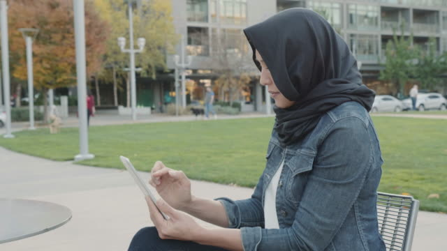 Slo Mo: Woman of Middle Eastern Descent Reading a Tablet on a Park Bench