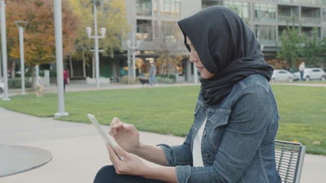 vídeos de stock e filmes b-roll de slo mo: woman of middle eastern descent reading a tablet on a park bench - banco de parque