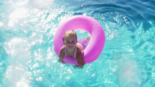 slo mo young girl playing in a swimming pool - swimming pool stock videos & royalty-free footage