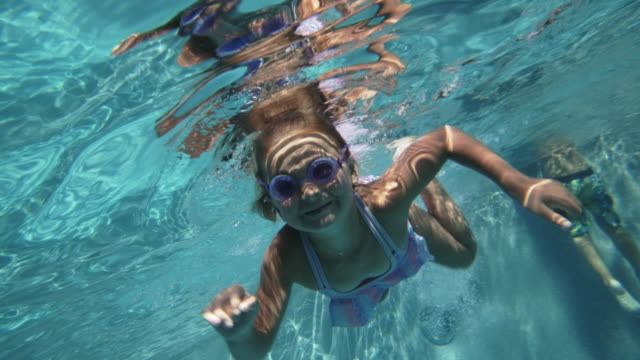 slo mo young girl swimming underwater in a swimming pool - 8 9 jahre stock-videos und b-roll-filmmaterial
