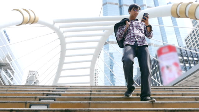 Slo Mo Young Man using smartphone , walking
