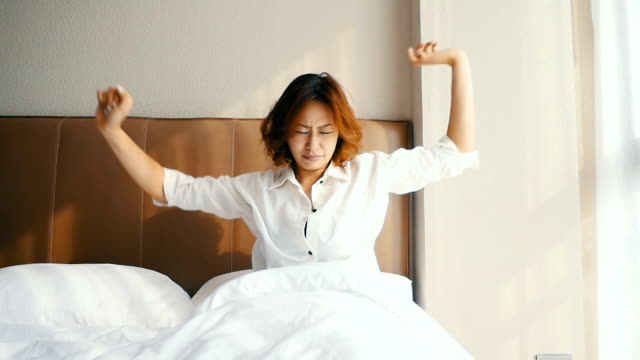 Slo Mo Young woman waking up in white bed