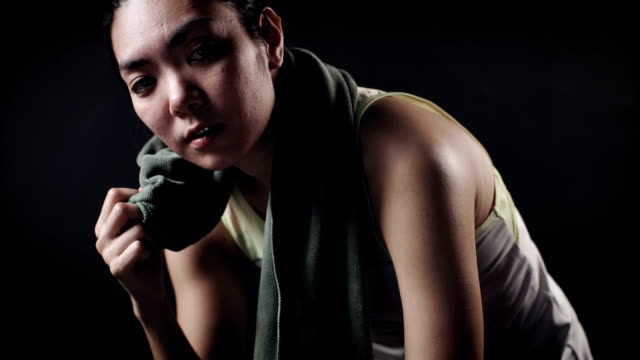 Slo motion : Athletic asian woman sweating and resting